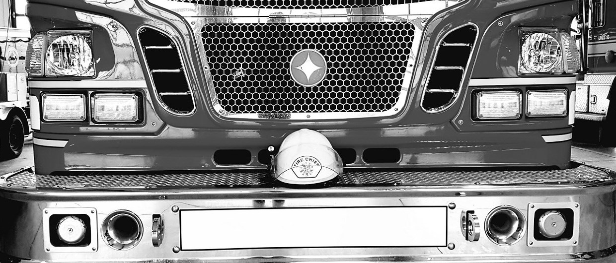 Black and white picture of fire chief white helmet on front bumper of fire truck
