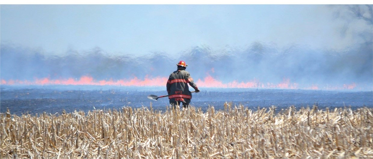 North Perth Fire fighter looking onto a field fire